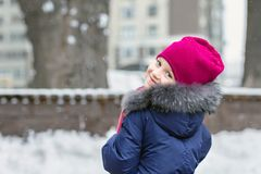 Portrait of happy adorable child laughing on city street during snowfall. Cute little caucasian girl in knitted hat and scarf and. Dawn jacket having fun royalty free stock image