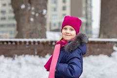 Portrait of happy adorable child laughing on city street during snowfall. Cute little caucasian girl in knitted hat and scarf and. Dawn jacket having fun stock photo
