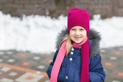 Portrait of happy adorable child laughing on city street during snowfall. Cute little caucasian girl in knitted hat and scarf and. Dawn jacket having fun royalty free stock images