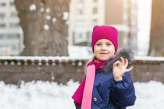 Portrait of happy adorable child showing OK sigh. Cute little caucasian girl in knitted hat and scarf and dawn jacket having fun. Playing outdoor in winter stock images