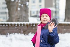 Portrait of happy adorable child showing OK sigh. Cute little caucasian girl in knitted hat and scarf and dawn jacket having fun. Playing outdoor in winter stock image