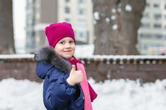 Portrait of happy adorable child showing OK sigh. Cute little caucasian girl in knitted hat and scarf and dawn jacket having fun. Portrait of happy adorable stock photo