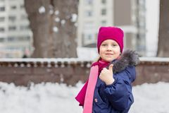 Portrait of happy adorable child showing thumbs up sign. Cute little caucasian girl in knitted hat and scarf and dawn jacket. Having fun playing outdoor in stock image