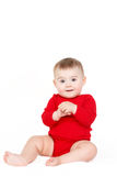 Portrait of a happy adorable Infant child baby girl lin red sitting happy smiling on a white background Stock Photo