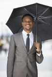 Portrait of a happy African American businessman holding umbrella Royalty Free Stock Photography