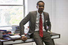 Portrait of happy African American businessman sitting on office desk Stock Photo