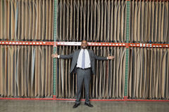 Portrait of happy African American businessman standing arms outstretched in front of thin veneer sheets Stock Photo