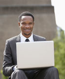 Portrait of a happy African American businessman using laptop Stock Images