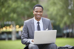 Portrait of a happy African American businessman using laptop in park Royalty Free Stock Photo