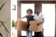Portrait happy African American couple on moving day in new house. Smiling black men and women standing in hall with cardboard boxes in hands, looking in stock photography