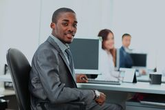 Portrait of a happy African American entrepreneur displaying computer laptop in office. Royalty Free Stock Photo