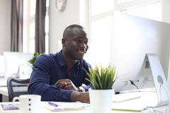Portrait of a happy African American entrepreneur displaying computer in office. Portrait of a happy African American entrepreneur displaying computer in office royalty free stock images