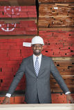 Portrait of happy African American male contractor with stacked wooden planks in background Royalty Free Stock Photography
