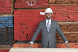 Portrait of happy African American male contractor standing in front of stacked wooden planks Royalty Free Stock Images
