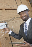 Portrait of happy African American male contractor using tablet PC while inspecting wooden planks Stock Photos