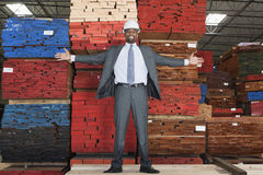 Portrait of happy African American male engineer standing with arms outstretched in front of stacked wooden planks stock photos