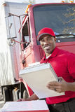 Portrait of a happy African American man holding clipboard with delivery truck in background Royalty Free Stock Image