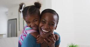 Portrait of happy african american mother and daughter hugging at home