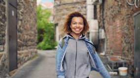 Portrait of happy African American teenager walking and dancing in the street then looking at camera and smiling stock video footage