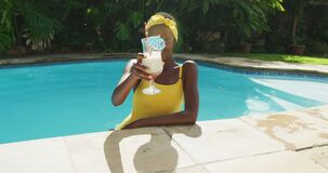 Portrait of happy african american woman standing in swimming pool making a toast with her drink