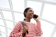 Happy african american woman talking with mobile phone at the station royalty free stock images
