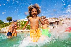 African boy playing with friends in shallow water. Portrait of happy African boy splashing while playing with friends in shallow water, spending summertime at stock image