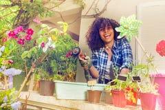 African girl teenager having fun watering flowers stock image