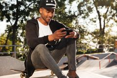 Portrait of a happy african guy using mobile phone. Portrait of a happy african guy skateboarder using mobile phone while having rest in urban zone Stock Image