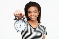 Portrait of a happy african teen girl showing alarm clock Royalty Free Stock Photography