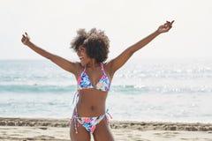 Happy afro american woman in bikini raising hands on beach Royalty Free Stock Photo