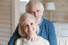 Portrait of happy aged couple hugging making picture together stock photography
