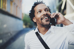 Portrait of happy American African black man using mobile phone to call friends at sunny street.Concept of happy young. Portrait of happy American African black Stock Photo