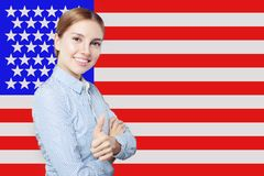 Portrait of happy american girl with thumb up against the USA flag background. Travel and learn english language concept royalty free stock image