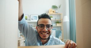 Portrait of happy Arabian man opening carton box smiling looking at camera. Expressing positive emotions receiving present. Youth and happiness concept stock video footage