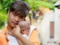 Portrait of happy Asia father holding his newborn sweet baby dressed in white clothes. The father embracing his baby with love and. Care. his daughter always stock photo
