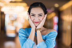 Happy Asian girl in shopping mall. Portrait of happy Asian beautiful girl wih trendy stylist dress with modern shopping mall background. Attractive smile woman Royalty Free Stock Image