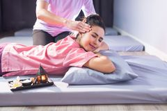 Thai massage to happy Asian woman. Portrait of happy Asian beautiful woman relax in spa. Body care treatment by Thai massage. Cute girl with traditional dress Stock Photo