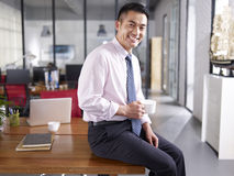 Portrait of a happy asian business executive in office. An asian businessman holding cup of coffee sitting on desk in office, smiling and cheerful Stock Photos