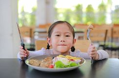 Portrait of happy Asian child girl eating Pork steak and vegetable salad on the table with holding knife and fork. Children having stock images