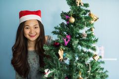 Portrait of happy Asian Chinese girl with Santa Claus hat celebrate Christmas near xmas tree to enjoy 2018 holiday and 2019 new. Year stock photos