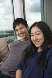 Portrait of happy Asian couple sitting on sofa at home Royalty Free Stock Photo