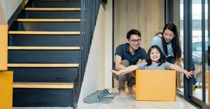 Portrait of happy Asian family moving to new house with cardboard boxes and playing cardboard box. royalty free stock image