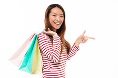 Portrait of a happy asian girl holding shopping bags Royalty Free Stock Photography