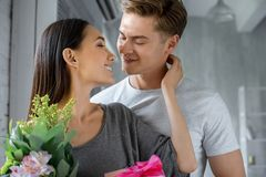 Portrait of happy asian girlfriend with present and bouquet of flowers looking at caucasian boyfriend. At home stock images