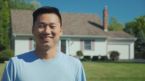 Portrait of a happy Asian man on the background of a new home. Looking at the camera, smiling. Successful purchase of. Real estate concept stock photos