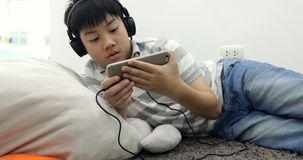 Portrait of a happy asian preteen boy lying awake with smart phone and headphones and listening to music at home. stock video