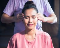 Head Thai massage to beauty girl. Portrait of happy Asian smile beautiful woman relax in spa. Body care treatment by Thai massage. Cute girl with traditional royalty free stock images