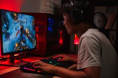 Portrait of happy asian teenage gamer boy playing video games on. Computer in dark room wearing headphones and using backlit colorful keyboard royalty free stock images