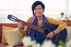 Pretty woman playing guitar. Portrait of happy Asian woman playing guitar and singing Royalty Free Stock Photos