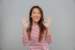 Portrait of a happy asian woman showing ok gesture. With two hands and looking at camera isolated over gray background Stock Image